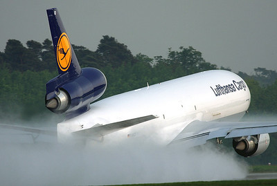 20090501_FRA: After a brief rainshower this departing MD-11F is creating a splash zone on RWY 18 at FRA.